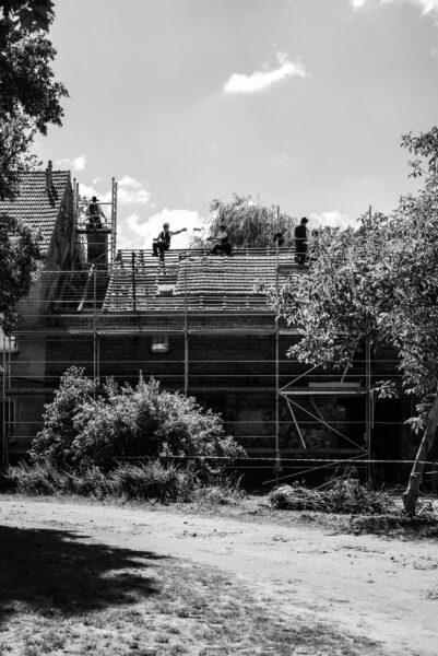 Wandergesellen bauen unter den Dachstuhl des Bullenstalls.